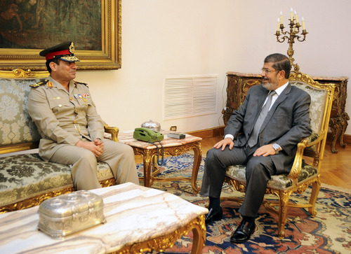FILE - In this Monday, Aug. 13, 2012 file photo, Egyptian Minister of Defense, Lt. Gen. Abdel-Fattah el-Sissi, left, meets with Egyptian President Mohammed Morsi in Cairo, Egypt. Egypt's powerful military is showing signs of growing impatience with the country's Islamist leaders, criticizing their policies and issuing thinly-veiled threats that it might seize power again. The tension is raising the specter of another military intervention in politics much like the one in 2011, when generals ousted longtime authoritarian leader Hosni Mubarak to end the 18-day popular uprising. (AP Photo/Egyptian Presidency, File)