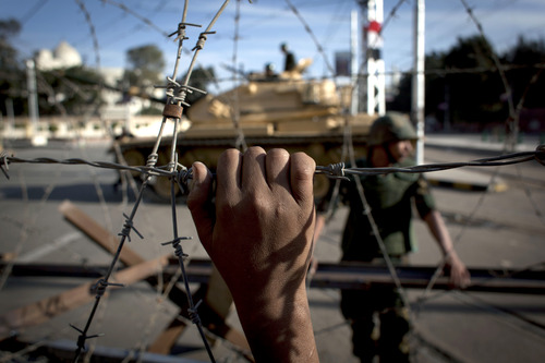 FILE - In this Thursday, Dec. 6, 2012 file photo, an Egyptian army tank is seen behind barbed wire securing the perimeter of the presidential palace while protesters on the other side chant anti President Mohammed Morsi slogans, in Cairo, Egypt. Egypt's powerful military is showing signs of growing impatience with the country's Islamist leaders, criticizing their policies and issuing thinly-veiled threats that it might seize power again. The tension is raising the specter of another military intervention in politics much like the one in 2011, when generals ousted longtime authoritarian leader Hosni Mubarak to end the 18-day popular uprising. (AP Photo/Nasser Nasser, File)
