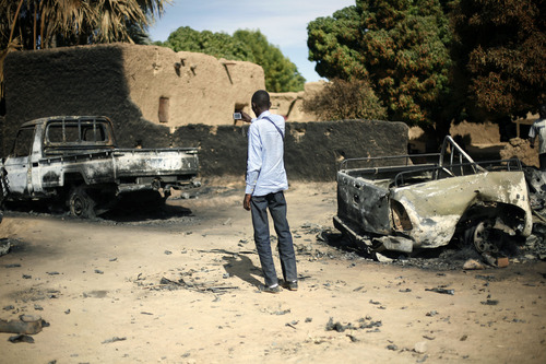 FILE In this Jan. 21, 2013 file photo, an unidentified man takes a picture of  the charred remains of  trucks used by radical Islamists, on the outskirt of Diabaly, Mali. An instruction on camouflaging cars is one of 22 tips on how to avoid drones, listed on a document left behind by the Islamic extremists as they fled northern Mali from a French military intervention in January. The tip sheet, found Feb. 6 by an AP reporter in Timbuktu, reflects how al-Qaida's chapter in North Africa anticipated a military intervention that would make use of drones, as the battleground in the war on terror worldwide is shifting from boots on the ground to unmanned planes in the air.(AP Photo/Jerome Delay, File)