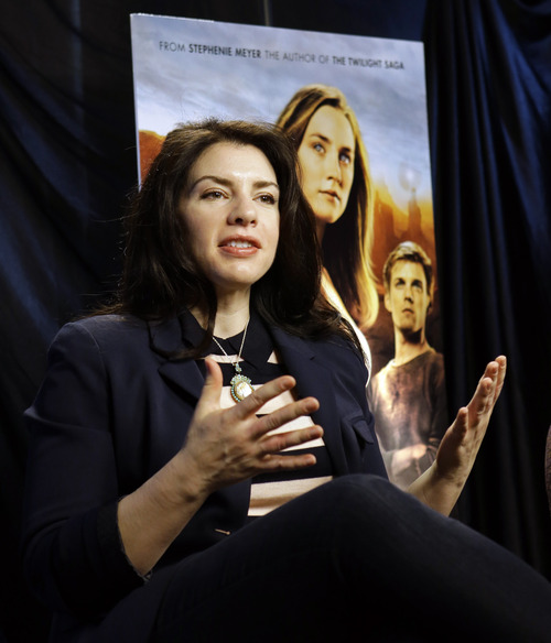 """This Feb. 19, 2013 photo shows author Stephenie Meyer speaking in Miami. Meyer, author of the """"Twilight"""" saga, wrote """"The Host"""" as an escape from editing of one of the books in the popular vampire series. The movie adaption of """"The Host"""" premieres March 29. (AP Photo/Alan Diaz)"""
