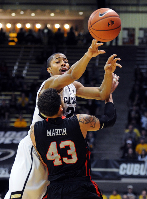 Colorado's Spencer Dinwiddie, rear, passes over Utah's Cedric Martin during the first half of their NCAA college basketball game, Thursday, Feb. 21, 2013, in Boulder, Colo. (AP Photo/The Daily Camera, Cliff Grassmick) NO SALES; MAGS OUT; TV OUT