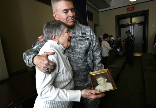 Scott Sommerdorf   |  The Salt Lake Tribune Jefferson S. Burton, adjutant general of the Utah National Guard, hugs Alice Telford, who holds a photo of her son, John William Telford, Wednesday, February 20, 2013. Telford handed over the photo of her son who died serving in Vietnam to the effort to collect photos of veterans for the Vietnam Memorial in Washington, D.C., in a ceremony at the Utah State Capitol.