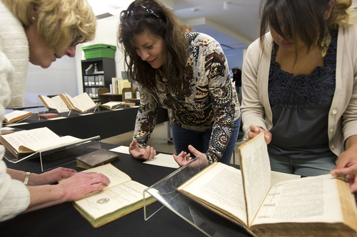 Lennie Mahler  |  The Salt Lake Tribune Luise Poulton (left), curator and head of rare books at the Marriott Library, Robyn Anderson and Rebeca Granillo examine a collection of first-edition ancient astronomy books in the special collections area of the Marriott Library, Wednesday, Jan. 30, 2013.