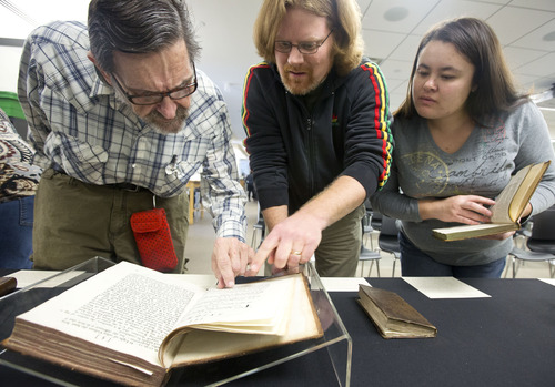 "Lennie Mahler  |  The Salt Lake Tribune Ray Druian, Steve Peay and Tera Peay examine a first edition of Isaac Newton's ""Opticks"" in the special collections area of the Marriott Library."