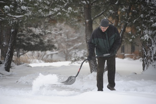 Keith Houin shovels his sidewalk in Springs Colo. following an overnight snowstorm Thursday, Feb. 21, 2013.  Winter storm warnings were issued from eastern Colorado through Illinois Thursday. (AP Photo/The Colorado Springs Gazette, Mark Reis)