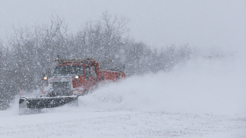 A plow tries to clear K-10 highway near DeSoto, Kan., Thursday, Feb. 21, 2013. The Kansas Turnpike Authority encouraged drivers to stay off the turnpike entirely; it runs from Oklahoma to Kansas City. There was virtually zero visibility on the turnpike early Thursday. And I-70 and other major highways in Kansas were snowpacked and icy, according to the Kansas Department of Transportation. Kansas Gov. Sam Brownback closed executive offices, except for essential personnel. He urged residents to have an extra cup of coffee, get out a board game and play with their children. (AP Photo/Orlin Wagner)