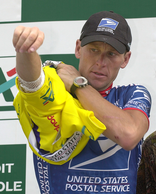 FILE - In this June 14, 2003 file photo, U.S. Postal Service leader Lance Armstrong puts on the overall leader's yellow jersey after the 6th stage of the 55th Criterium du Dauphine Libere cycling race between Challes Les Eaux and Briancon, French Alps. Lawyers for Armstrong say the Justice Department has joined a lawsuit against the cyclist. The lawsuit alleges the former Tour de France champion concealed his use of performance-enhancing drugs for over a decade and defrauded his long-time sponsor, the U.S. Postal Service.  (AP Photo/Patrick Gardin, File)