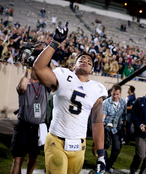"In this Sept. 15, 2012 photo, Notre Dame linebacker Manti Te'o points to the sky as he leaves the field after a 20-3 win against Michigan State in East Lansing, Mich. In a shocking announcement, Notre Dame said Te'o was duped into an online relationship with a woman whose ""death"" from leukemia was faked by perpetrators of an elaborate hoax. (AP Photo/South Bend Tribune, James Brosher) MANDATORY CREDIT"