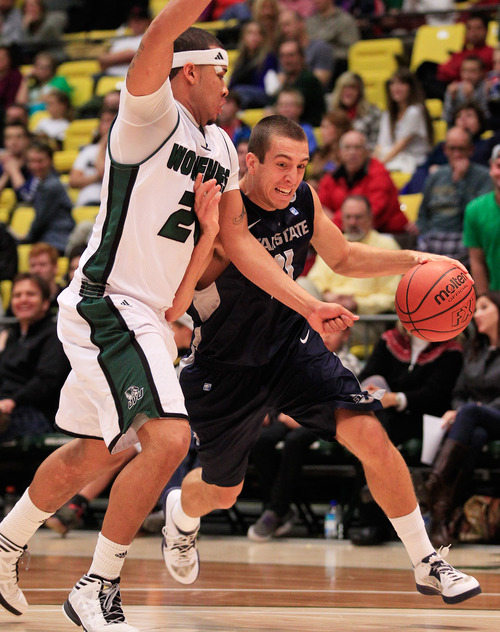 Utah State's Spencer Butterfield drives around UVU's Alfonzo Hubbard during the NCAA basketball game between Utah Valley University and Utah State in Orem on Saturday, Dec. 15, 2012. SPENSER HEAPS/Daily Herald