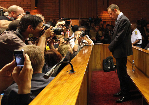 Olympic athlete Oscar Pistorius stands in the dock during his bail hearing at the magistrates court in Pretoria, South Africa, Friday, Feb. 22, 2013. The fourth and likely final day of Oscar Pistorius' bail hearing opened on Friday, with the magistrate then to rule if the double-amputee athlete can be freed before trial or if he has to remain in custody over the shooting death of his girlfriend. (AP Photo/Themba Hadebe)