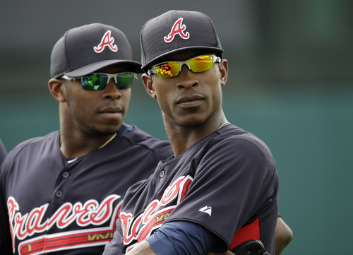 Atlanta Braves outfielders Justin Upton, left, and his brother B.J. Upton, right, listen to a coach during a spring training baseball workout Wednesday, Feb. 20, 2013, in Kissimmee, Fla. (AP Photo/David J. Phillip)