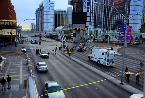 FILE - In this Feb. 21, 2013 file photo, law enforcement personal investigate the scene of a multi-vehicle accident and shooting in Las Vegas. Variously known as an adult playground and Disneyland for grown-ups, Las Vegas has worked to brand itself as a place where tourists can enjoy a sense of edginess with no real danger. But a series of high-profile and seemingly random incidents that have left visitors to the Strip dead or in the hospital is threatening Sin City's reputation as a padded room of a town where people can cut loose with no fear of consequences. (AP Photo/Las Vegas Review-Journal, Jeff Scheid, File) LOCAL TV OUT; LOCAL INTERNET OUT; LAS VEGAS SUN OUT