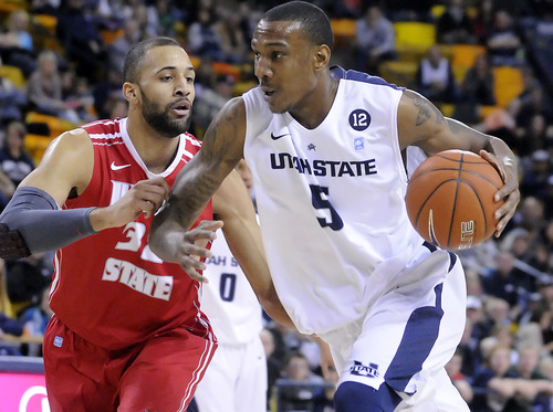 Utah State center Jarred Shaw (5) drives to the basket as Illinois State forward Jackie Carmichael defends  during an NCAA college basketball game Saturday, Feb. 23, 2013, in Logan, Utah. (AP Photo/The Herald Journal, Eli Lucero)