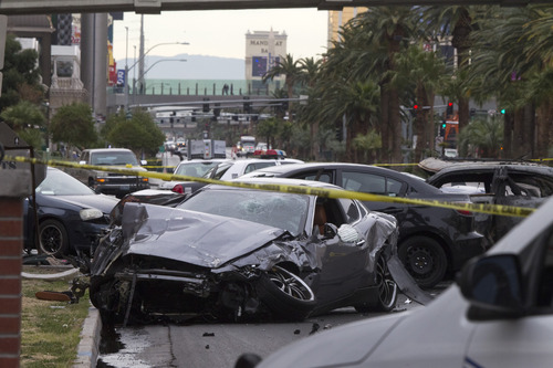 Police rope off the scene of  a shooting and multi-car accident on the Las Vegas Strip in Las Vegas early Thursday, Feb. 21, 2013.  Authorities say at least one person in a Range Rover shot at people in a Maserati that then crashed into a taxi cab. The taxi cab burst into flames, and the driver and passenger were killed. The male driver of the Maserati also died, and his passenger was shot. (AP Photo/Las Vegas Sun, Steve Marcus)