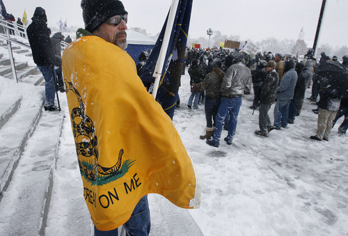 """Scott Sommerdorf      The Salt Lake Tribune """"All Day Joe"""" (last name withheld) stands wrapped in a tea party flag as he rallies along with about 200 other gun-rights activists at the Utah Capitol as part of the """"National Day of Resistance"""" Saturday, February 23, 2013."""