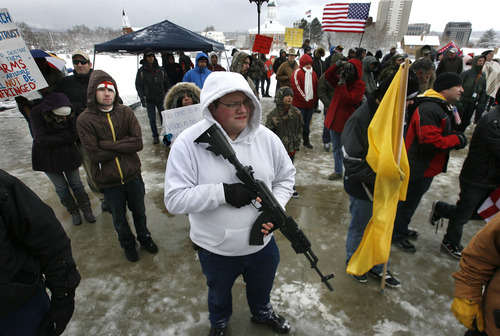 """Scott Sommerdorf      The Salt Lake Tribune A man who identified himself as """"Grim,"""" holding an AK-47, listens to speeches as he and about 200 other gun-rights activists rally at the Utah Capitol as part of the """"National Day of Resistance"""" Saturday, February 23, 2013."""