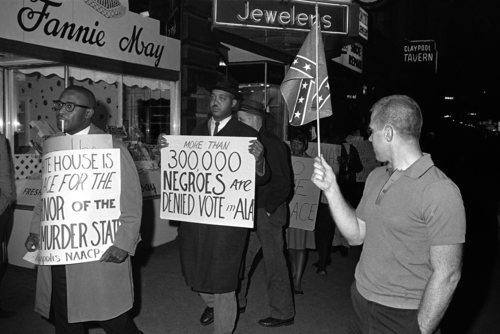 """FILE - In this April 14, 1964 black-and-white file photo, a man holds a Confederate flag at right, as demonstrators, including one carrying a sign saying: """"More than 300,000 Negroes are Denied Vote in Ala"""", demonstrate in front of an Indianapolis hotel where then-Alabama Governor George Wallace was staying. After more than a century, the Census Bureau is dropping use of the word """"Negro"""" to describe black Americans in its surveys. Instead of the term popularized during the Jim Crow era of racial segregation, census forms will use the more modern-day labels, """"black"""" or """"African-American.""""  (AP Photo/Bob Daugherty, File)"""