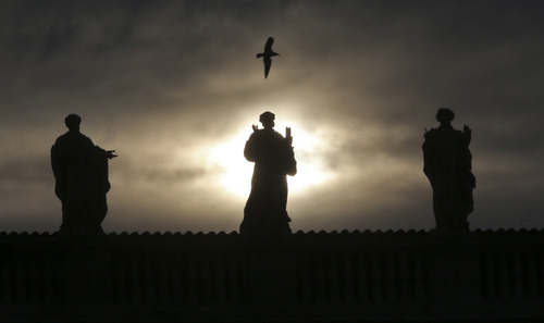 A seagull flies over statues at St. Peter's Basilica at the Vatican, Monday, Feb. 25, 2013. Pope Benedict XVI has changed the rules of the conclave that will elect his successor, allowing cardinals to move up the start date if all of them arrive in Rome before the usual 15-day transition between pontificates. Benedict signed a legal document, issued Monday, with some line-by-line changes to the 1996 Vatican law governing the election of a new pope. It is one of his last acts as pope before resigning Thursday. (AP Photo/Dmitry Lovetsky)