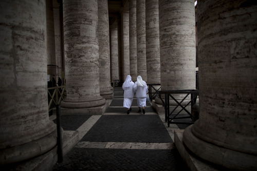 Two nuns walk under the Bernini colonnade in St. Peter's Square at the Vatican, Monday, Feb. 25, 2013. Pope Benedict XVI has changed the rules of the conclave that will elect his successor, allowing cardinals to move up the start date if all of them arrive in Rome before the usual 15-day transition between pontificates. Benedict signed a legal document, issued Monday, with some line-by-line changes to the 1996 Vatican law governing the election of a new pope. It is one of his last acts as pope before resigning Thursday. (AP Photo/Oded Balilty)
