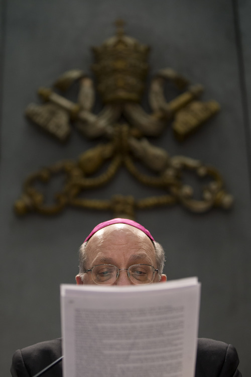 Archbishop Pier Luigi Celata, Vice Chamberlain, reads a copy of a document signed by Pope Benedict XVI, a press conference, at the Vatican, Monday, Feb. 25, 2013. Pope Benedict XVI has changed the rules of the conclave that will elect his successor, allowing cardinals to move up the start date if all of them arrive in Rome before the usual 15-day transition between pontificates. Benedict signed a legal document, issued Monday, with some line-by-line changes to the 1996 Vatican law governing the election of a new pope. It is one of his last acts as pope before resigning Thursday.  (AP Photo/Andrew Medichini)