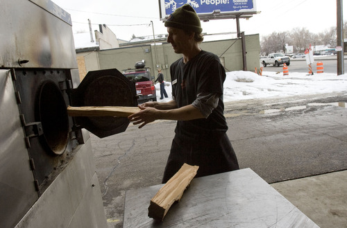 Kim Raff  |  The Salt Lake Tribune Loren MacLaren stocks the bbq smoker with wood outside of Sugarhouse BBQ Company in Salt Lake City on Friday February 22, 2013. Sugarhouse BBQ Company is moving to 2100 S. 900 East. Owners say the Trolley project will cut down on their parking so they will be forced to move from their current location at 2207 S. 700 East.