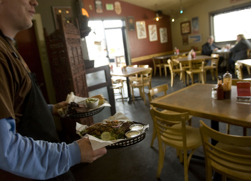 Kim Raff  |  The Salt Lake Tribune A waiter brings plates of food to customers in the dining room of Sugarhouse BBQ Company in Salt Lake City on Friday, February 22, 2013. Sugarhouse BBQ Company is moving to 2100 S. 900 East. Owners say the Trolley project will cut down on their parking so they will be forced to move from their current location at 2207 S. 700 East.