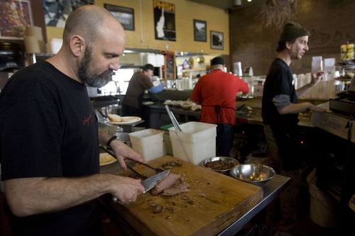 Kim Raff  |  The Salt Lake Tribune Manager Jeffrey Berg slices brisket while preparing meals at Sugarhouse BBQ Company in Salt Lake City on Friday, February 22, 2013. Sugarhouse BBQ Company is moving to 2100 S. 900 East. Owners say the Trolley project will cut down on their parking so they will be forced to move from their current location at 2207 S. 700 East.