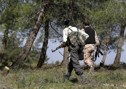 Free Syrian Army fighters from the Knights of the North brigade move to reconnaissance a Syrian army forces base of al-Karmid, at Jabal al-Zaweya, in Idlib province, Syria, Wednesday, Feb. 27, 2013. Syrian warplanes carried out airstrikes on rebels trying to storm a police academy outside Aleppo on Wednesday, while jihadi fighters battled government troops along a key supply road leading to the southeastern part of the city, activists said. (AP Photo/Hussein Malla)