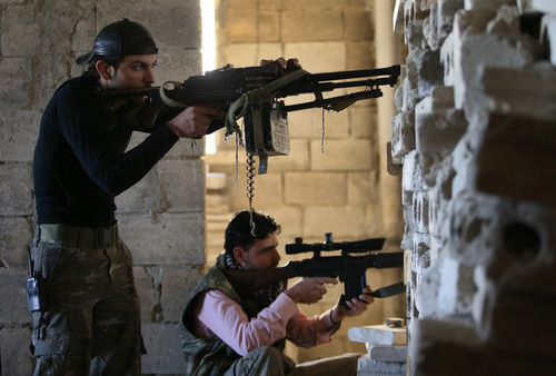Free Syrian Army fighters, take their positions as they observe the Syrian army forces base of Wadi al-Deif, at the front line of Maarat al-Nuaman town, in Idlib province, Syria, Tuesday Feb. 26, 2013. Syrian rebels battled government troops near a landmark 12th century mosque in the northern city of Aleppo on Tuesday, while fierce clashes raged around a police academy west of the city, activists said. (AP Photo/Hussein Malla)