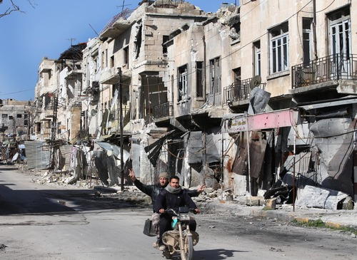 Syrians ride a scooter as one gestures,  as they pass by a destroyed street which was damaged by the shelling of the Syrian forces, at Maarat al-Nuaman town, in Idlib province, Syria, Tuesday Feb. 26, 2013. Syrian rebels battled government troops near a landmark 12th century mosque in the northern city of Aleppo on Tuesday, while fierce clashes raged around a police academy west of the city, activists said. (AP Photo/Hussein Malla)