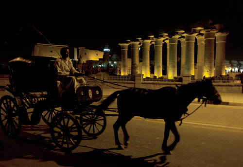 A cart passes the Luxor Temple while roaming the streets for customers, in Luxor, Egypt, Tuesday, Feb. 26, 2013. A hot air balloon carrying tourists over Egypt's ancient city of Luxor caught fire Tuesday, and some passengers trying to escape the flames leaped to their deaths before the craft crashed in a sugar cane field. At least 19 tourists were killed in one of the world's deadliest ballooning accidents. (AP Photo/Nasser Nasser)