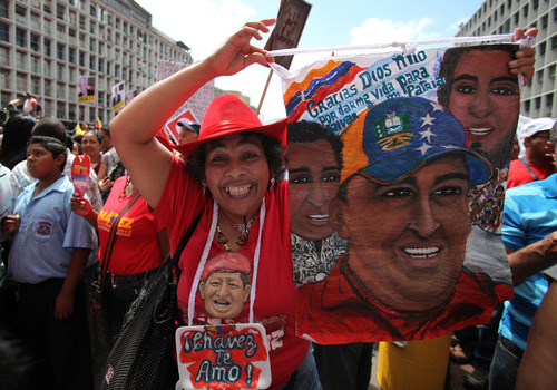 """A supporter of Venezuela's President Hugo Chavez holds a painting of the ailing leader during an event to commemorate the violent street protests of 1989 known as the """"Caracazo,""""  in Caracas, Venezuela, Wednesday, Feb. 27, 2013. The wave of the1989 violent protests, seen by the Chavez government as a """"popular uprising,"""" was in response to the economic measures imposed by then President Carlos Andres Perez. (AP Photo/Fernando Llano)"""
