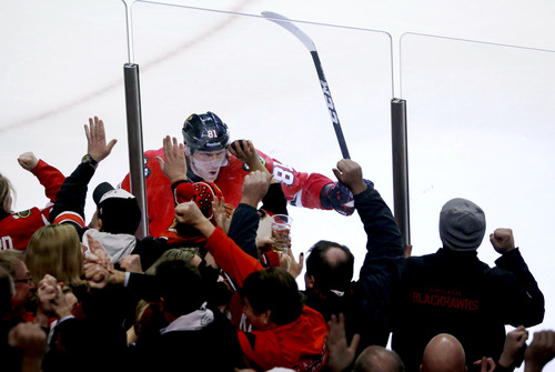 Chicago Blackhawks right wing Marian Hossa, of Slovakia, celebrates along the boards with fans after scoring the winning goal during overtime of an NHL hockey game against the Edmonton Oilers, Monday, Feb. 25, 2013, in Chicago. The Blackhawks won 3-2. (AP Photo/Charles Rex Arbogast)