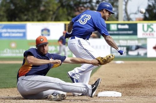 Toronto Blue Jays' Brett Lawrie, top, collides with Houston Astro's Nate Freiman to reach first base on a dropped third strike in the fourth inning of a spring training exhibition baseball game, Wednesday, Feb. 27, 2013, in Dunedin, Fla. Houston won 10-1. (AP Photo/Matt Slocum)