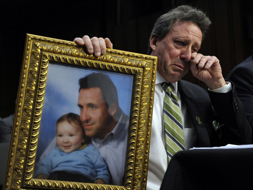 Neil Heslin, the father of a 6-year-old boy who was slain in the Sandy Hook massacre in Newtown, Conn., on Dec. 14, holds a picture of himself with his son Jesse and wipes his eye while testifying on Capitol Hill in Washington, Wednesday, Feb. 27, 2013, before the Senate Judiciary Committee on the Assault Weapons Ban of 2013. (AP Photo/Susan Walsh)