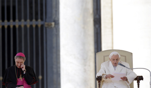 """Pope Benedict XVI's personal secretary George Gaenswein, left, wipes his eye as the Pope delivers his message during his last general audience in St. Peter's Square at the Vatican, Wednesday, Feb. 27, 2013. Pope Benedict XVI basked in an emotional sendoff Wednesday at his final general audience in St. Peter's Square, recalling moments of """"joy and light"""" during his papacy but also times of great difficulty. He also thanked his flock for respecting his decision to retire. (AP Photo/Gregorio Borgia)"""