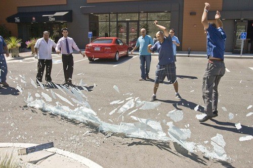 Paul Fraughton  |  The Salt Lake Tribune Mohsen Asgari  (center) smashes the frosted glass curtain from his bar at Vuda Bar and Winery in Draper on Aug. 26, 2011. The barrier was torn down when the establishment got a bar permit, which unlike restaurants, does not require barriers to hide bartenders from public view.