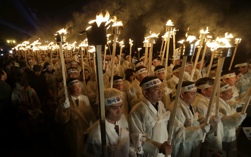 South Koreans, wearing traditional Korean costumes, carry torches as they march on a street during a ceremony to celebrate the March First Independence Movement Day, the anniversary of the 1919 uprising against Japanese colonial rule, in Cheonan, south of Seoul, South Korea, Thursday, Feb. 28, 2013. (AP Photo/Lee Jin-man)