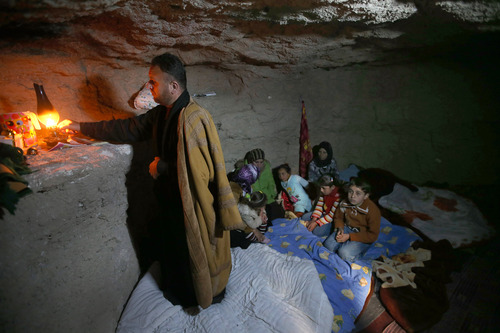A defected Syrian policeman, Adnan al-Hamod, 33, lights a kerosene lamp at an underground cave used for shelter from Syrian governemnt forces shelling and airstrikes, at Jirjanaz village, in Idlib province, Syria, Thursday Feb. 28, 2013. Across northern Syria, rebels, soldiers, and civilians are making use of the country's wealth of ancient and medieval antiquities to protect themselves from Syria's two-year-old war. They are built of thick stone that has already withstood centuries, and are often located in strategic locations overlooking towns and roads. (AP Photo/Hussein Malla)