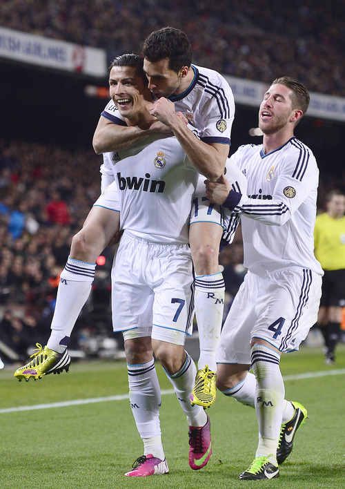 Real Madrid's Cristiano Ronaldo, left, from Portugal, Alvaro Arbeloa, center, and Sergio Ramos celebrate after scoring against FC Barcelona during a Copa del Rey soccer match at the Camp Nou stadium in Barcelona, Spain, Tuesday, Feb. 26, 2013. Ronaldo scored twice to lead Real Madrid to a 3-1 win and a spot in the Copa del Rey final. (AP Photo/Manu Fernandez)