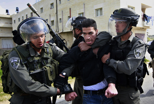 Isreali border policemen arrest a Palestinian man during a protest to support Palestinian prisoners, outside Ofer, an Israeli military prison near the West Bank city of Ramallah, Thursday, Feb. 28, 2013. (AP Photo/Majdi Mohammed)