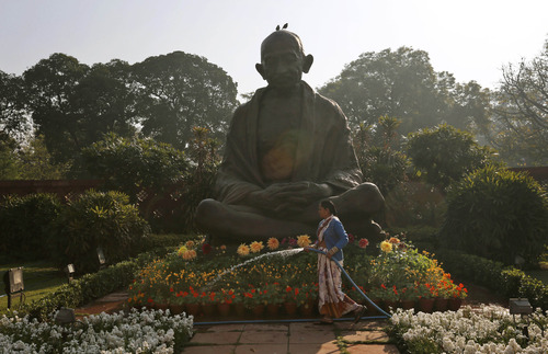 A worker waters plants around a statue of Mahatma Gandhi inside the premises of Parliament as Indian Finance Minister Palaniappan Chidambaram delivers the annual budget in New Delhi, India, Thursday, Feb. 28, 2013. India's finance minister has unveiled the national budget with a promise to set Asia's third largest economy back onto a path of high growth and to check runaway inflation and the fiscal deficit.  (AP Photo/ Saurabh Das)