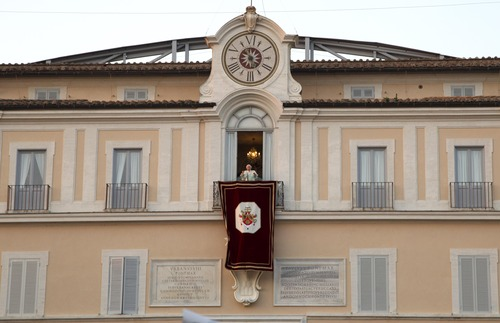 Pope Benedict XVI speaks from the balcony window of the Pontifical summer residence in Castel Gandolfo, some 35 kilometers south of Rome, to a cheering crowd gathered to see him off the day he ends his pontificate, Thursday, Feb. 28, 2013. (AP Photo/Domenico Stinellis)