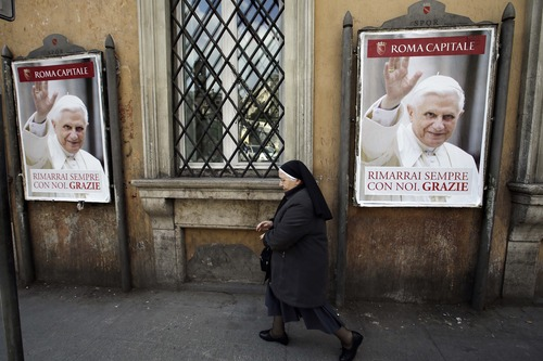 "A nun walks past posters of Pope Benedict XVI reading in Italian, "" You will stay always with us. Thank you"" along a street in Rome, Thursday, Feb. 28, 2013. Shortly before 5 p.m. on Thursday, Benedict will leave the Apostolic palace inside the Vatican for the last time as pontiff, head to the helipad at the top of the hill in the Vatican gardens and fly to the papal retreat at Castel Gandolfo south of Rome. There, at 8 p.m. sharp, Benedict will become the first pontiff in 600 years to resign. (AP Photo/Gregorio Borgia)"