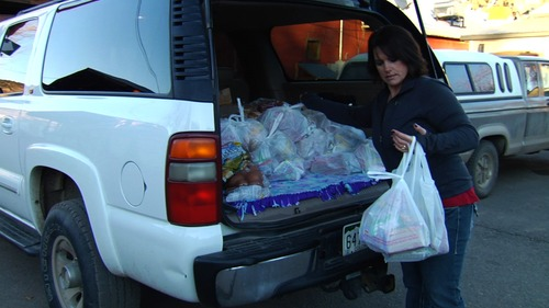 "Courtesy photo Leslie Nichols, a teacher in a Colorado town, delivers food-bank packages to families of her students, in a moment from the documentary ""A Place at the Table."" The film discusses the problem of hunger in America."
