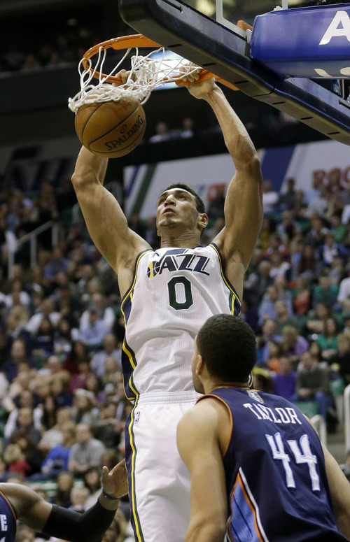 Utah Jazz's Enes Kanter (0) dunks the ball as Charlotte Bobcats' Jeffery Taylor (44) looks on in the second half during an NBA basketball game Friday, March 1, 2013, in Salt Lake City. The Jazz defeated the Bobcats 98-68. (AP Photo/Rick Bowmer)