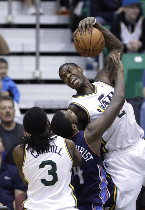 Utah Jazz's Marvin Williams (2) pulls down a rebound in front of Charlotte Bobcats' Michael Kidd-Gilchrist (14) while Utah Jazz's DeMarre Carroll (3) looks on in the second quarter of an NBA basketball game Friday, March 1, 2013, in Salt Lake City. (AP Photo/Rick Bowmer)