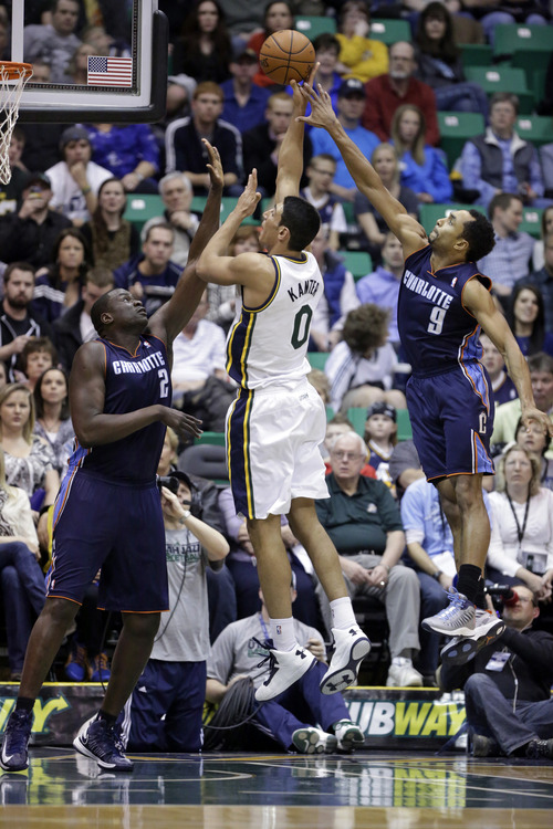 Utah Jazz's Enes Kanter (0) shoots as Charlotte Bobcats' DeSagana Diop (2) and teammate Gerald Henderson (9) defend in the first quarter during an NBA basketball game, Friday, March 1, 2013, in Salt Lake City. (AP Photo/Rick Bowmer)