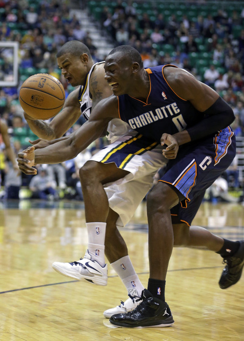 Charlotte Bobcats' Bismack Biyombo (0) and Utah Jazz's Earl Watson (11) chase the loose ball in the first quarter during an NBA basketball game Friday, March 1, 2013, in Salt Lake City.  (AP Photo/Rick Bowmer)