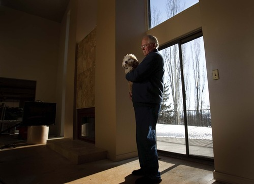 Leah Hogsten  |  The Salt Lake Tribune Roy Bosley, 65, stands in his Ogden home holding his dog that his friends helped him rescue from a shelter to ease his grief. His wife, Carol, died in November 2009 of an overdose on painkillers.